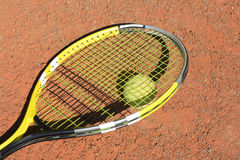 Tennis-racket and ball. Tennis-racket with one ball laying on the court Stock Images