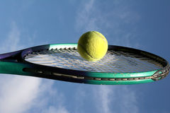 Tennis racket and ball. Yellow tennis ball in centre of tennis racket Royalty Free Stock Image