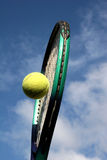 Tennis racket and ball. Yellow tennis ball in centre of tennis racket Royalty Free Stock Photography