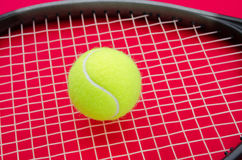 Tennis racket with ball on alerted red background. Tennis ball on a raquet with a red alerted serious background suggesting an important match set game or point Stock Photos