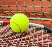 Tennis racket with ball on it clay on clay court royalty free stock photo