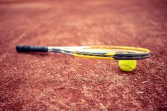 Tennis racket and ball on clay tennis court Stock Images