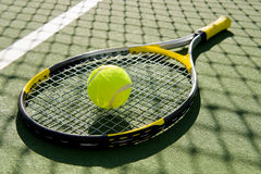 Tennis Racket and Ball on Court. A tennis racket and new tennis ball on a freshly painted tennis court royalty free stock photography