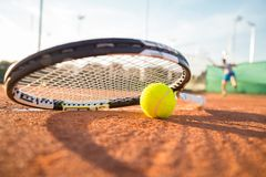 Tennis racket and ball on court. Close-up tennis racket and ball placed on court ground while player hitting ball Stock Image