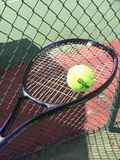 Tennis racket, ball and fence. Purple and black tennis racket with a yellow Wilson tennis ball balancing on top. Tennis court and fence in the background. Great Royalty Free Stock Photos