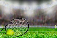 Tennis Racket and Ball on Grass Court With Copy Space. Low angle view of tennis racket and ball on grass court with deliberate shallow depth of field on brightly Royalty Free Stock Photo