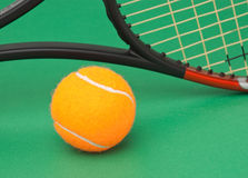 Tennis racket and ball on green background. Tennis racket and ball on a green background royalty free stock image