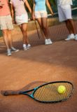 Tennis racket and ball on hard court. Players at background Royalty Free Stock Photo
