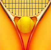 Tennis racket and ball. On hot orange background stock photography