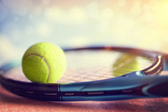 Tennis racket and ball. Tennis ball resting on top of a tennis racquet on a red asphalt court royalty free stock photography