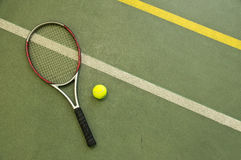 Tennis racket and ball. Wallpaper. Tennis racket and ball on the court at the background. Wallpaper Stock Photo