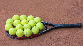 Tennis racket and balls on the clay court Royalty Free Stock Photo