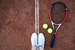 Tennis racket and tennis balls on the clay tennis court. royalty free stock photography