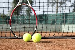 Tennis racket and balls on the clay tennis court. royalty free stock images