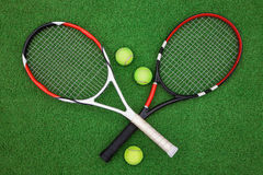 Tennis racket with balls on green grass. Tennis racket with ball on green grass playing field Royalty Free Stock Photo