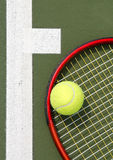Tennis racket close up. A close up of tennis racket head with a ball on it next to the line on a court Royalty Free Stock Photos
