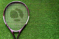 Tennis racket on green background top view.  Stock Image