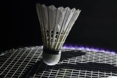 Tennis racket hitting shuttlecock. Side-lit tennis racket hitting shuttlecock in the tip Stock Photo