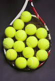Tennis Racket with a lot of Tennis balls on it Stock Image