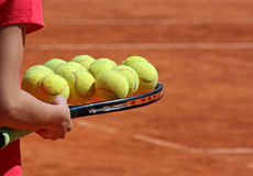 Tennis racket with several balls on it Stock Images