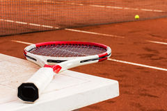 Tennis racket on the table, clay court, net and ball Royalty Free Stock Images