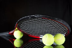 Tennis racket and three balls. Tennis racket and two balls for playing tennis on a black background Stock Photos
