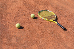 Tennis-racket and two balls. Tennis-racket with balls laying on the court Stock Image