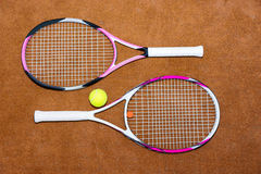 Tennis rackets with ball on a clay court outdoors. Sporty tennis rackets with ball on a clay court outdoors Royalty Free Stock Image
