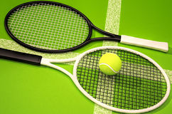 Tennis rackets and ball on a green background. Stock Photos