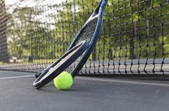 Tennis rackets and ball leaning on net Royalty Free Stock Photo