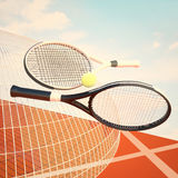Tennis rackets, ball, tennis court and light blue sky. Royalty Free Stock Photo