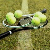 Tennis rackets with balls on hard surface court. Stock Image