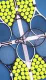 Tennis rackets with balls on hard surface court. Royalty Free Stock Photo