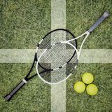 Tennis rackets and balls are located on grass court. Top view. Royalty Free Stock Images