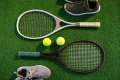 Tennis rackets with balls and sports shoes Stock Images