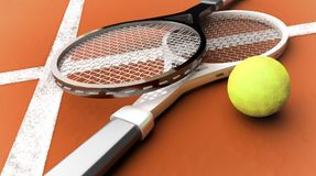 Tennis rackets near a yellow ball on a brick red court. Royalty Free Stock Images
