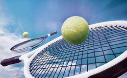 Tennis rackets and yellow balls on against the blue sky. royalty free stock images