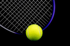 Tennis Racquet and Ball on Black Background. Tennis racquet and tennis ball isolated against a black background Royalty Free Stock Image