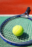 Tennis racquet and ball on the clay tennis court. Close up of tennis racquet and ball on the clay tennis court Stock Image