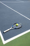 Tennis racquet and ball in court. On a sunny day Royalty Free Stock Photography