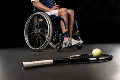 Tennis racquet with ball and disabled sportsman sitting in wheelchair behind Stock Photo