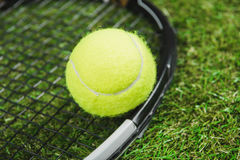 Tennis racquet and ball on green grass. Close-up view of tennis racquet and ball on green grass Stock Photo