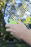 Tennis racquet and ball in hands. Hand holding tennis racquet and ball Royalty Free Stock Photo