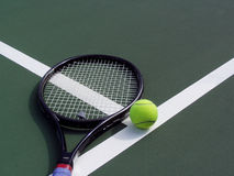 Tennis racquet and Ball on a tennis court. Shot of a tennis racquet with yellow tennis ball lying on the t-line of tennis court Royalty Free Stock Photo