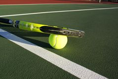 Tennis Racquet on court. Tennis racquet on top ob ball on tennis court Royalty Free Stock Photography