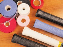 Tennis racquet handles with a variety of fresh grips. Installed with a range of over grip materials on rolls in the background. These grips offer a  range of Stock Photo