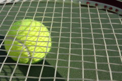 Tennis racquet with a tennis ball beneath. On a green court Stock Photography