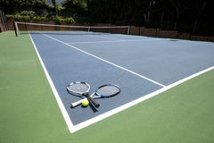 Tennis racquets and ball in court. On a sunny day Royalty Free Stock Image