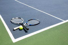Tennis racquets and ball in court. On a sunny day Stock Images