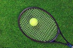 Tennis raquet and ball on grass. A tennis raquet or racket and yellow ball on grass Stock Photos